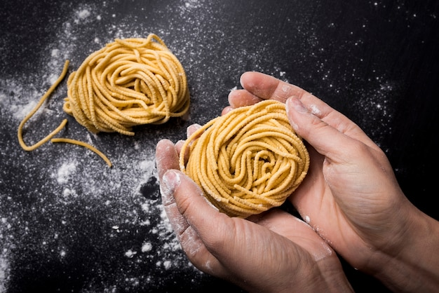 High angle view of chef holding spaghetti pasta nest over kitchen worktop