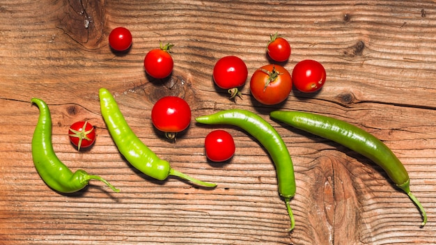 High angle view of chili peppers and cherry tomatoes on wooden backdrop