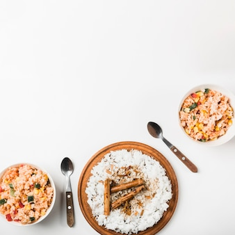 High angle view of chinese fried and steam rice with cinnamon sticks on white backdrop