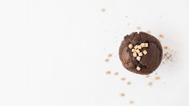High angle view of chocolate cupcake with caramel candies toppings on white background