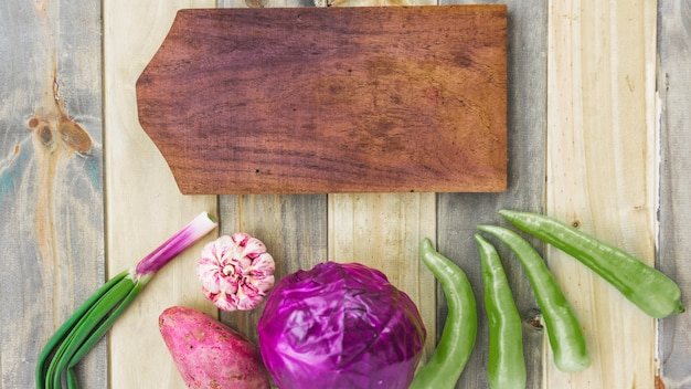 High angle view of chopping board with fresh healthy vegetables on wooden surface