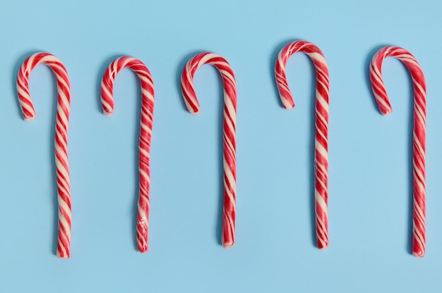 High angle view of christmas decoration. flat lay composition of five sweet candy canes, christmas lollipops lying on blue background with copy space for advertising