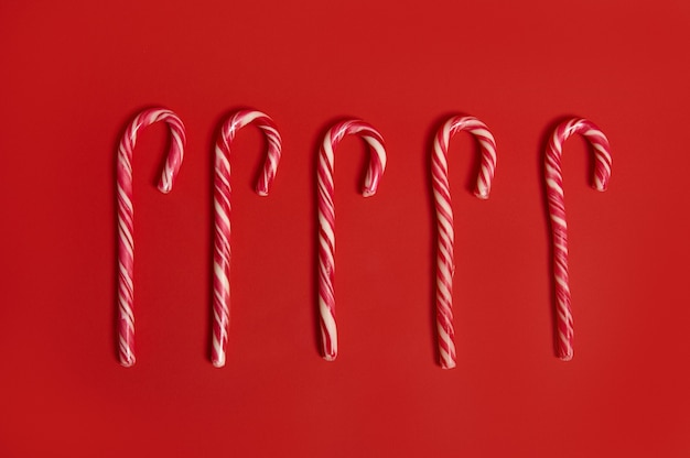 High angle view of christmas decoration. flat lay composition of five sweet candy canes, christmas lollipops lying on red background with copy space for advertising