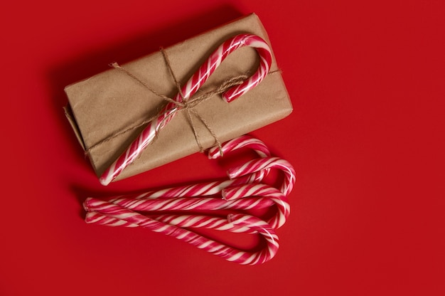 High angle view of christmas traditional items. striped candy cane on a present wrapped in kraft wrapping gift paper and lollipops lying on red background with copy space for new year advertising