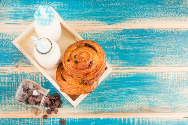 High angle view of cinnamon bun and milk bottles in wooden tray near spilled choco chips from glass jar
