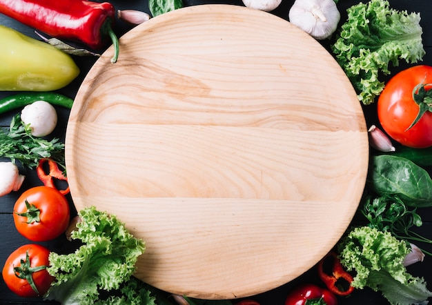 High angle view of circular wooden plate surrounded with fresh vegetables