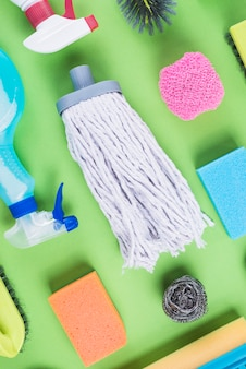 High angle view of cleaning items on green backdrop