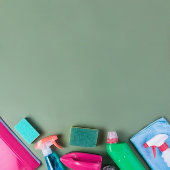 High angle view of cleaning supplies on green background