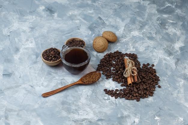 Chicchi di caffè di alta vista in ciotole con tazza di caffè, biscotti, cannella, caffè istantaneo in cucchiaio di legno su fondo di marmo azzurro. orizzontale
