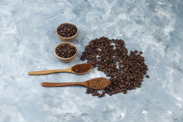 High angle view coffee beans in bowls with instant coffee and coffee flour in wooden spoons on light blue marble background. horizontal