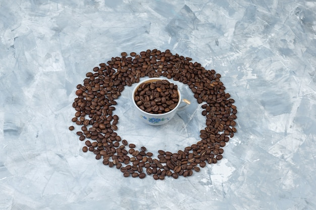 High angle view coffee beans in cup on grey plaster background. horizontal