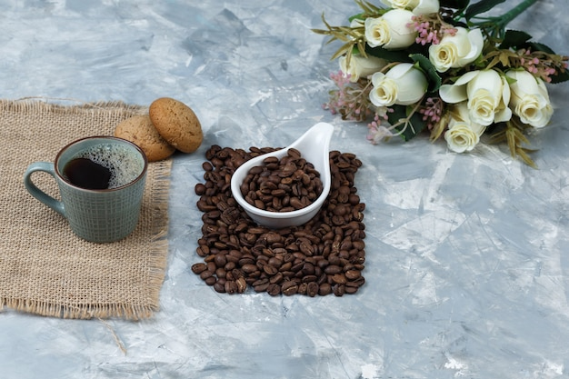 High angle view coffee beans in white porcelain jug with cookies, cup of coffee, flowers