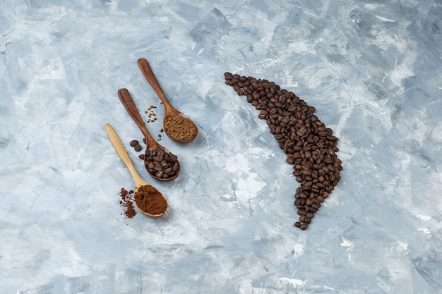 コーヒー豆、インスタントコーヒー、水色の大理石の背景に木のスプーンでコーヒー粉とハイアングルビューコーヒー豆。水平