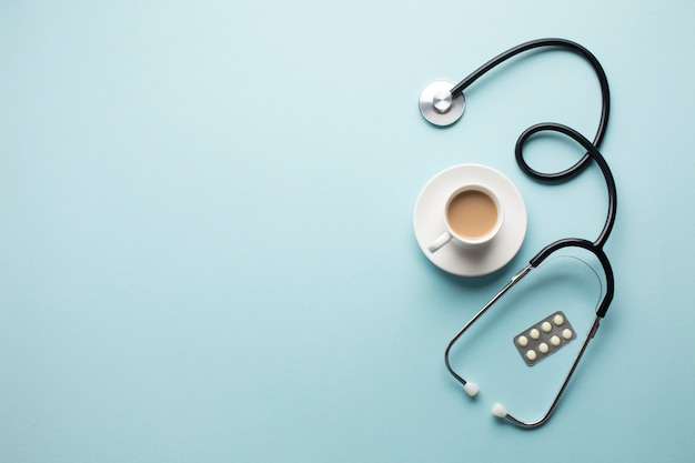 High angle view of coffee cup; stethoscope and medicine in blister pack over blue backdrop
