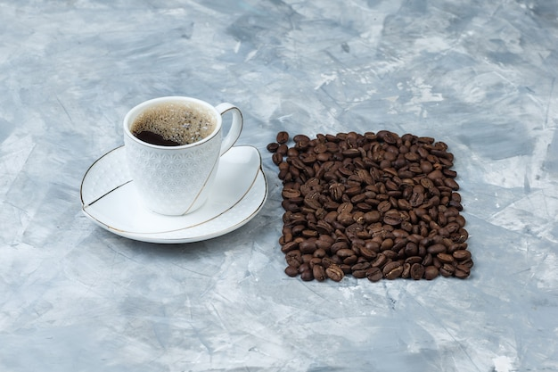 High angle view coffee in cup with coffee beans on blue marble background. horizontal