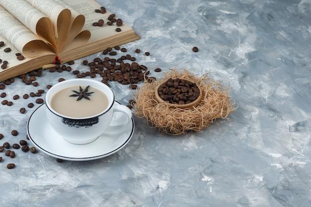 Vista di alto angolo caffè in tazza con chicchi di caffè, libro su sfondo grigio intonaco orizzontale