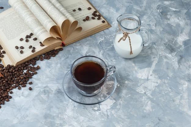 Caffè di vista di alto angolo in tazza con chicchi di caffè, libro, latte su sfondo grigio sgangherato. orizzontale