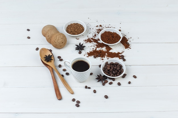 Caffè di vista di alto angolo in tazza con chicchi di caffè, caffè macinato, spezie, biscotti, cucchiai di legno su fondo di legno. orizzontale