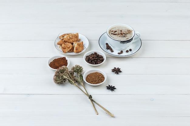 커피 콩, grinded 커피, 향신료, 쿠키, 나무 배경에 말린 허브 컵에 높은 각도보기 커피. 수평