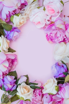 High angle view of colorful artificial flowers forming frame on pink background