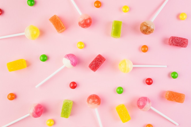 High angle view of colorful candies and lollipops on pink surface
