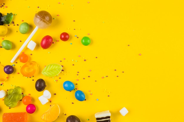 High angle view of colorful candies and lollipops on yellow backdrop