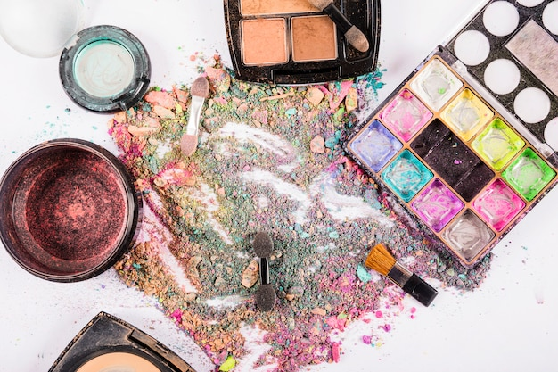 High angle view of colorful cosmetic powders on white surface