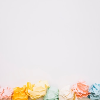 High angle view of colorful crumpled papers on white background