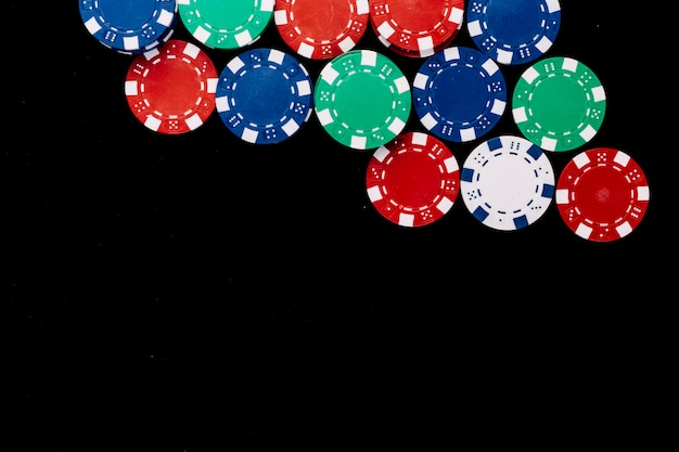 High angle view of colorful poker chips on black background