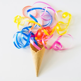 High angle view of colorful ribbons over waffle ice cream cone on white surface