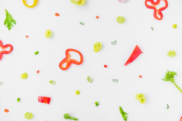 High angle view of colorful sliced vegetables on white background