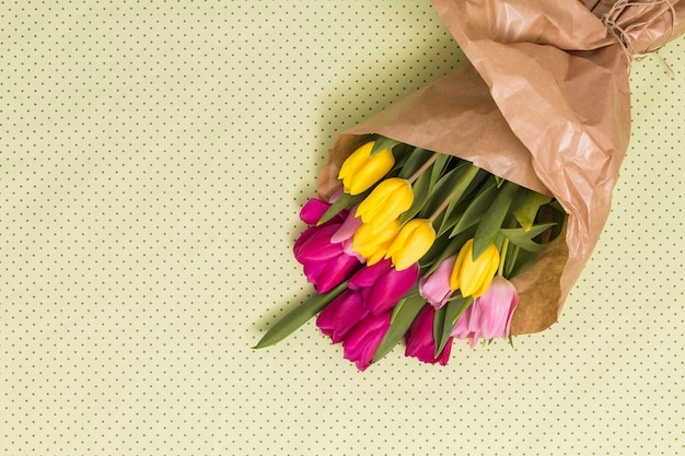 High angle view of colorful tulip flowers over yellow background