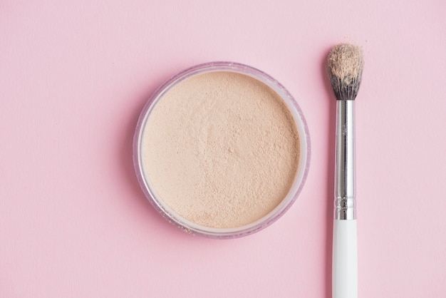 High angle view of compact powder and brush on pink backdrop