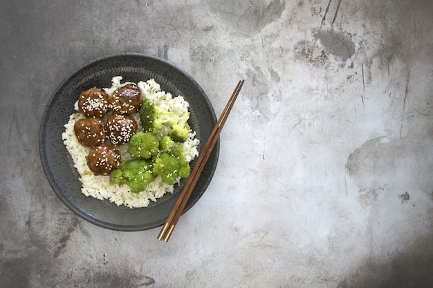 High angle view of cooked rice with meatballs and broccoli in a plate on the table with chopsticks