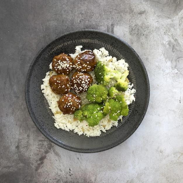 Vista dall'alto del riso cotto con polpette e broccoli in un piatto sul tavolo