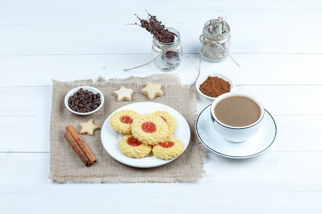 Biscotti di vista di alto angolo, cannella, chicchi di caffè sul pezzo di sacco con una tazza di caffè, una ciotola di caffè istantaneo, corde sul fondo del bordo di legno bianco orizzontale