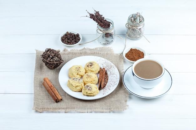 ハイアングルビュークッキー、シナモン、インスタントコーヒーのボウルと袋の部分のロープ、白い木の板の背景にコーヒーのカップ。水平