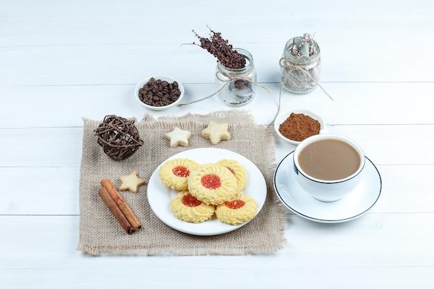 Biscotti di vista di alto angolo, cannella, corde sul pezzo di sacco con una ciotola di caffè istantaneo, tazza di caffè sul fondo del bordo di legno bianco. orizzontale
