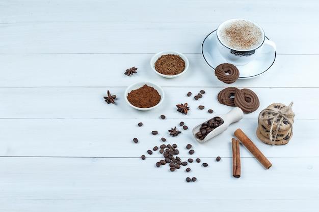 ハイアングルビュークッキー、インスタントコーヒーのボウル、コーヒー豆、白い木の板の背景にシナモンとコーヒーのカップ。水平