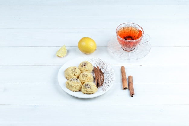 High angle view cookies, cup of tea with cinnamon, lemon on white wooden board background. horizontal