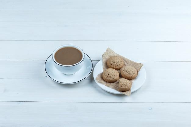 흰색 나무 보드 배경에 커피 한잔과 함께 흰색 접시에 높은 각도보기 쿠키. 수평