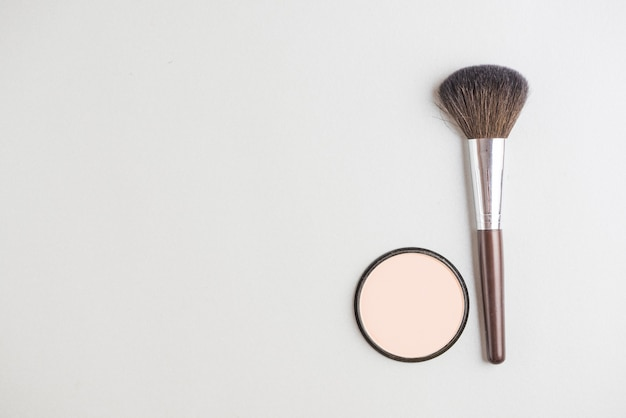 High angle view of cosmetic powder and brush on white backdrop