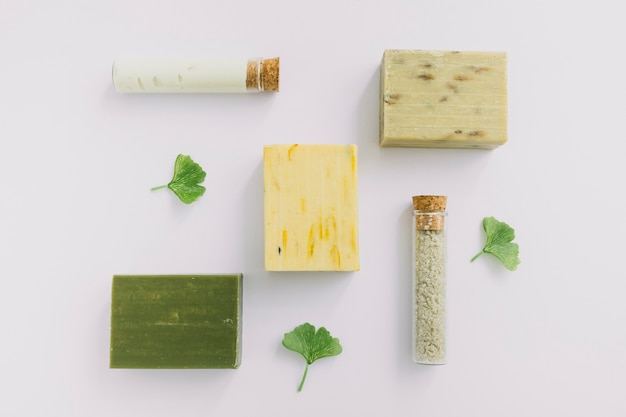 High angle view of cosmetic products and gingko leaf on white surface