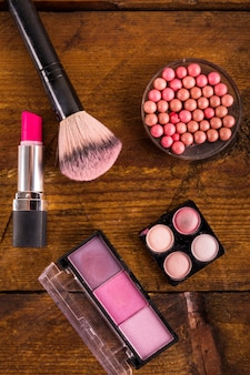 High angle view of cosmetic products with brush on wooden surface