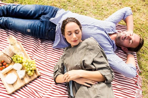 High angle view of couple sleeping on picnic blanket