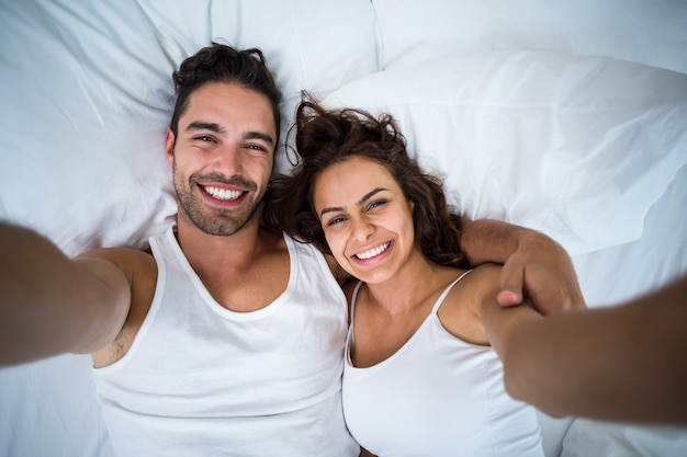 High angle view of couple taking self portrait on bed