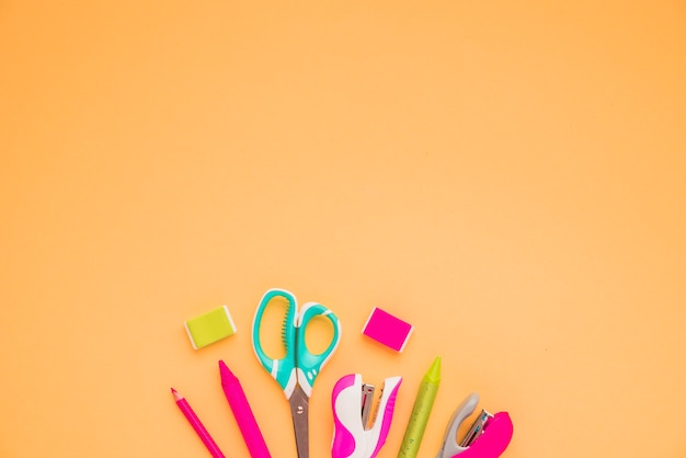 High angle view of craft supplies at the bottom of orange background