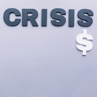High angle view of crisis word with dollar sign on grey backdrop