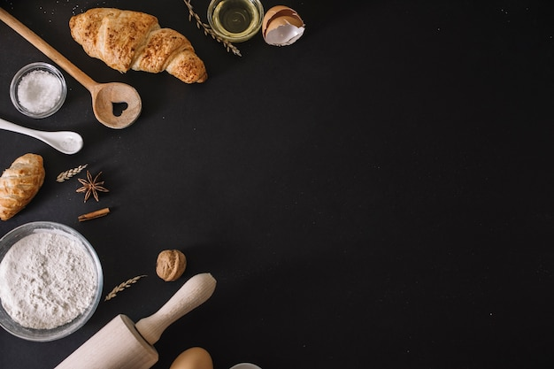 High angle view of croissants; baking ingredients and utensils on black surface