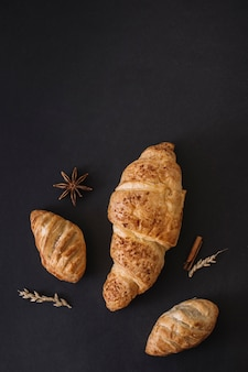 High angle view of croissants; spices and grains on black background